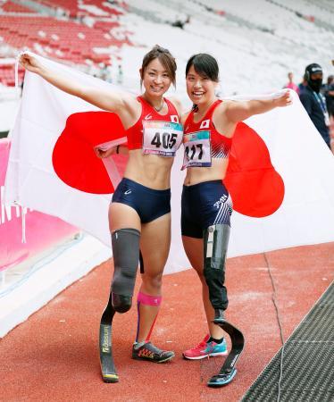 女子走り幅跳び(義足など)で優勝し、日の丸を掲げ笑顔を見せる中西麻耶(左)と3位の兎沢朋美=ジャカルタ(共同)
