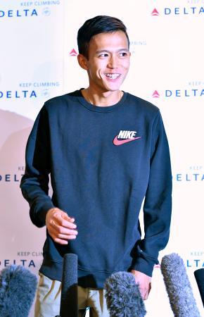 シカゴ・マラソンから帰国し、記者の質問に笑顔で答える大迫傑=10日、成田空港