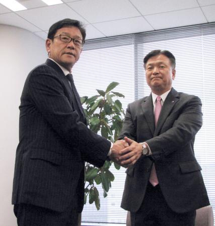 畑佳秀オーナー(右)と握手する日本ハムの栗山監督=19日、東京都内の日本ハム東京支社
