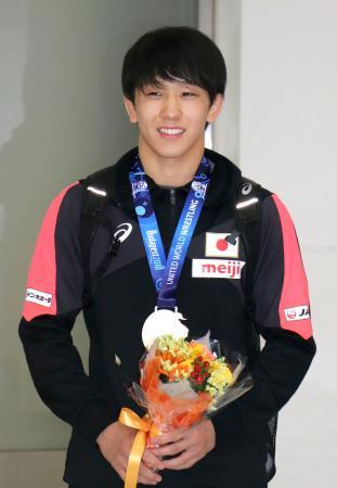 レスリングの世界選手権で獲得した金メダルを胸に帰国した乙黒拓斗=25日、成田空港
