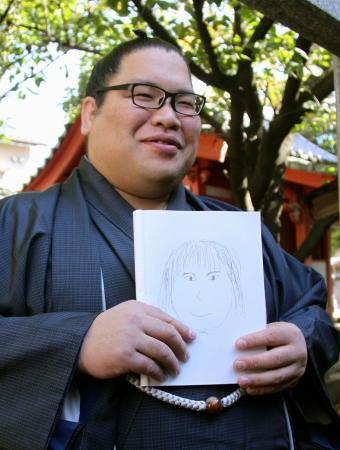 自ら描いた結婚相手の似顔絵を手に笑顔の錦木=29日午前、福岡市東区の伊勢ノ海部屋宿舎