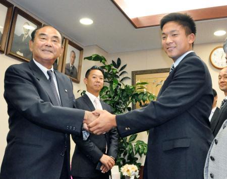 ドラフト4位指名のあいさつを受け、DeNAの吉田スカウト部長(左)と握手する日大鶴ケ丘高の勝又温史投手=31日、東京都杉並区