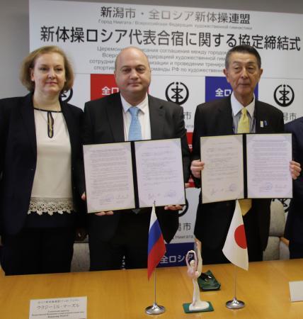 合宿地に関する協定を締結した新潟市の篠田昭市長(右)とロシアの新体操連盟のウラジーミル・マーズル氏(中央)=5日午前、新潟市