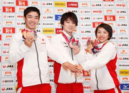 体操の世界選手権から帰国し、記者会見でメダルを手にする(左から)白井健三、内村航平、村上茉愛=5日、東京都渋谷区