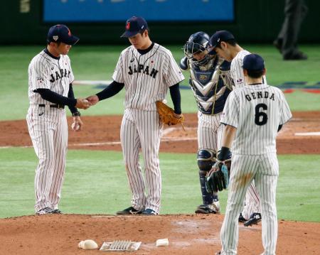 日本―MLB 5回、交代を告げられ、建山コーチ(左端)にボールを渡す多和田=東京ドーム