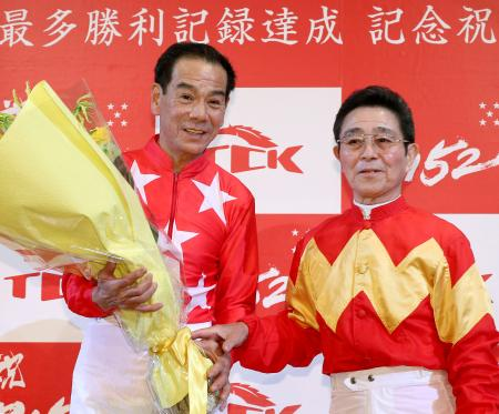 地方競馬の最多勝利記録更新の記念祝賀会で、佐々木竹見元騎手(右)から花束を受け取る的場文男騎手=17日夜、東京都内のホテル