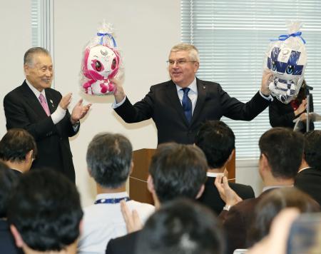 2020年東京五輪・パラリンピック組織委事務局を訪れ、笑顔で大会マスコットを手にするIOCのバッハ会長。左は森喜朗会長=28日午後、東京都港区