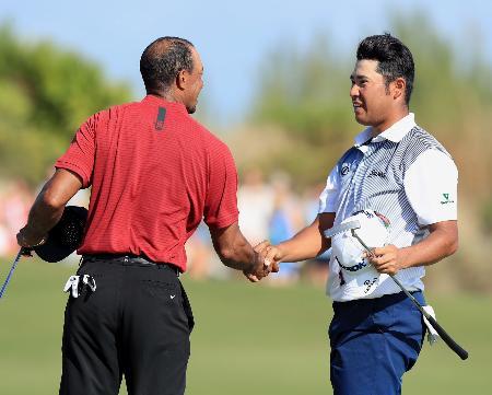 最終ラウンド、ホールアウトし、タイガー・ウッズ(左)と握手を交わす松山英樹=アルバニー・バハマ(共同)