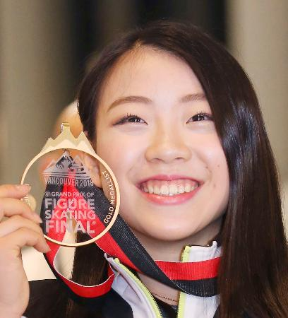 フィギュアスケートGPファイナルで優勝し帰国、金メダルを手に笑顔の紀平梨花選手=11日午後、成田空港