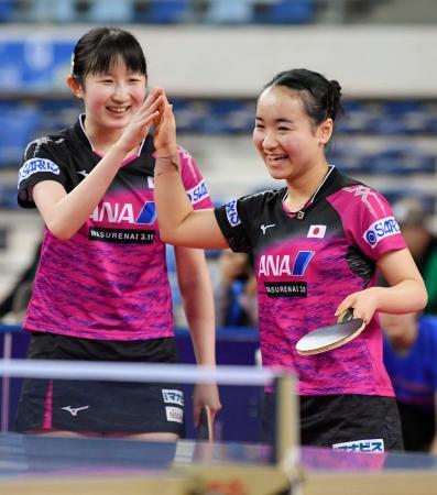 女子ダブルス準決勝で競り勝ち、笑顔でタッチを交わす早田(左)、伊藤組=仁川(共同)