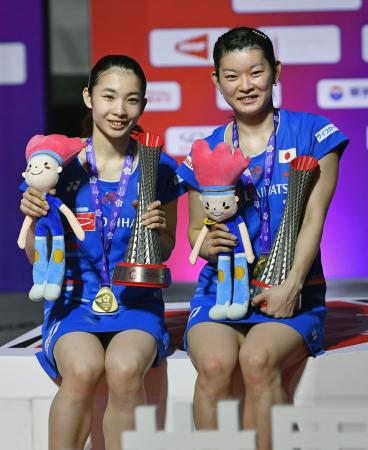 女子ダブルスで優勝し、トロフィーを手に笑顔の高橋礼(右)、松友組=広州(共同)