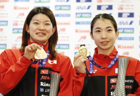 バドミントンのWTファイナルで女子ダブルスを制し、成田空港で金メダルを手に笑顔の高橋礼(左)、松友組=17日