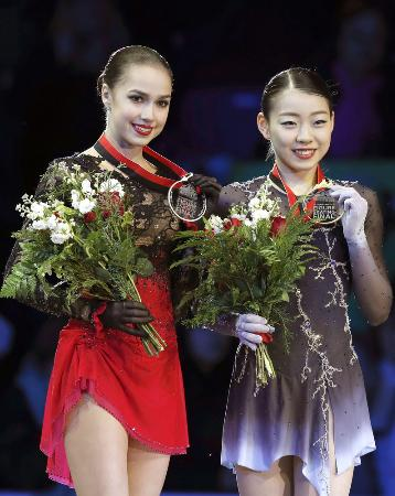 GPファイナル初出場で優勝し、表彰式で笑顔を見せる紀平梨花。左は2位のアリーナ・ザギトワ=バンクーバー(共同)