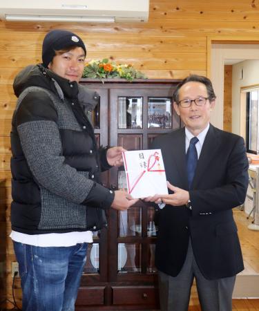 NPO法人「SOS子どもの村JAPAN」に寄付の目録を贈呈するソフトバンクの柳田(左)=24日、福岡市西区