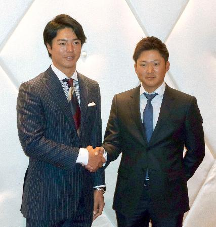 ジャパンゴルフツアー選手会の理事会を終え、握手する石川遼会長(左)と今平周吾副会長=4日、東京都内のホテル