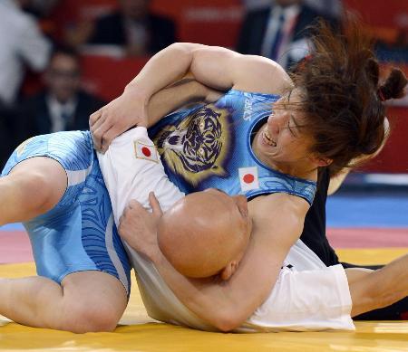 2012年のロンドン五輪女子55キロ級で優勝し、栄和人監督(下)を投げ飛ばす吉田沙保里選手(共同)