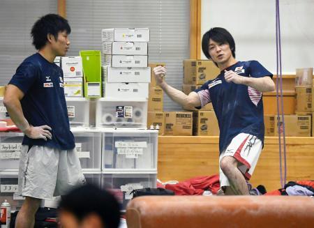 公開された強化合宿で、ポーズを取りながら談笑する内村航平(右)=東京都北区の味の素ナショナルトレーニングセンター