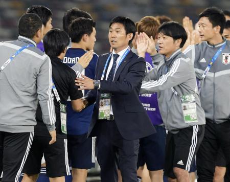 サッカーのアジア・カップで決勝トーナメント進出を決め、コーチらとタッチを交わす森保監督(中央)=13日、アブダビ(共同)