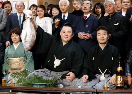 大相撲初場所で初優勝を決め、タイを手に笑顔の玉鷲。右は片男波親方=27日、東京都墨田区の片男波部屋