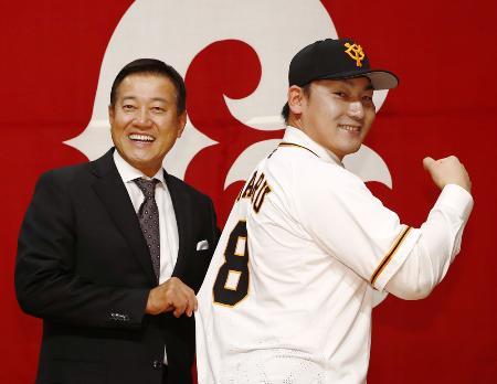 入団記者会見後、ユニホームを着てポーズを取る巨人の丸佳浩外野手(右)と原辰徳監督=2018年12月11日、東京都内のホテル
