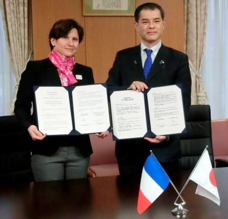 スポーツ分野での協力についての声明に署名した柴山文科相(右)とフランスのロクサナ・マラシネアヌ・スポーツ相=30日、文科省