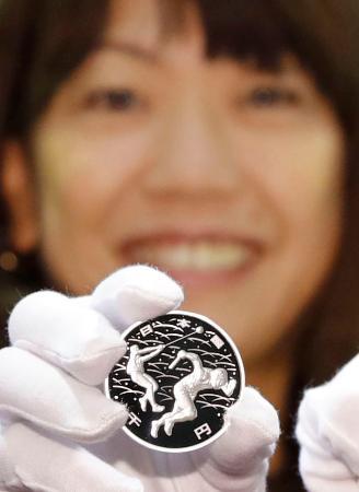 高橋尚子さんが手にする2020年東京五輪を記念した千円銀貨=7日午後、大阪市の造幣局