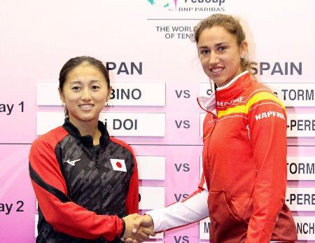 フェド杯の組み合わせ抽選が行われ、握手を交わす土居美咲(左)とスペインのサラ・ソリベストルモ=北九州市立総合体育館