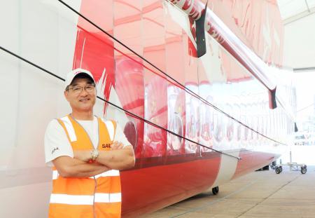 セーリングGPシリーズに参加する日本チームの早福和彦COO。後ろは日本の双胴船の帆=13日、シドニー(共同)