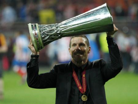 欧州リーグを制し、優勝カップを掲げるアトレチコ・マドリードのシメオネ監督=2012年5月、ブカレスト(ロイター=共同)