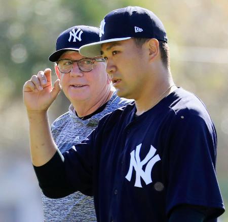対戦形式の練習で、ロスチャイルド投手コーチ(左)と話をするヤンキース・田中=タンパ(共同)