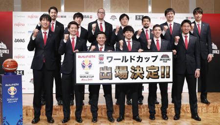 W杯出場を決め、帰国後の記者会見でポーズをとるバスケットボール男子の日本代表=25日夜、千葉県成田市