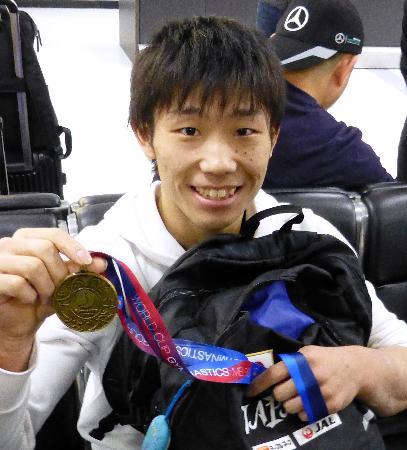 体操の種目別W杯シリーズ第2戦から帰国し、鉄棒で獲得した金メダルを手にする宮地秀享=25日、成田空港