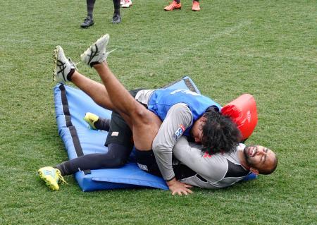 ラグビーの日本代表候補合宿でタックルを練習する稲垣(上)とリーチ=東京都町田市