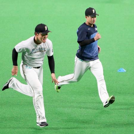 試合前の練習で、ダッシュする日本ハム・吉田輝。左は清宮=札幌ドーム