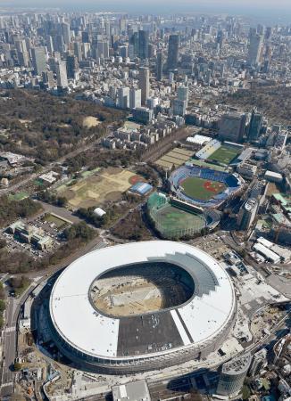 2020年東京五輪の開幕まで12日で500日。11月末に完成予定の新国立競技場は、難関とされた屋根部分の工事がほぼ終了していた。奥は選手村や競技施設が建設される臨海部=9日(共同通信社ヘリから)