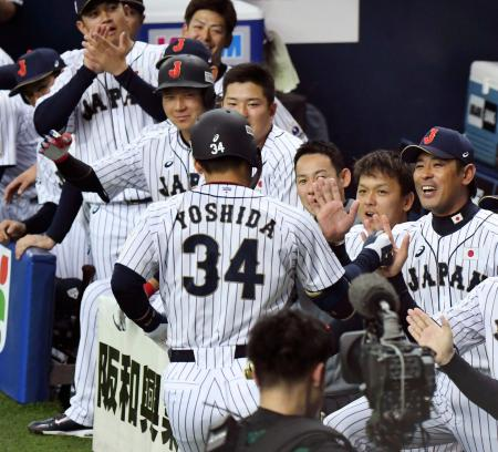 1回、先制の満塁本塁打を放った吉田正(34)を迎える稲葉監督(右端)ら日本ベンチ=京セラドーム