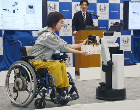 車いすの女性に飲み物が入ったかごを手渡すロボット=15日午前、東京都港区