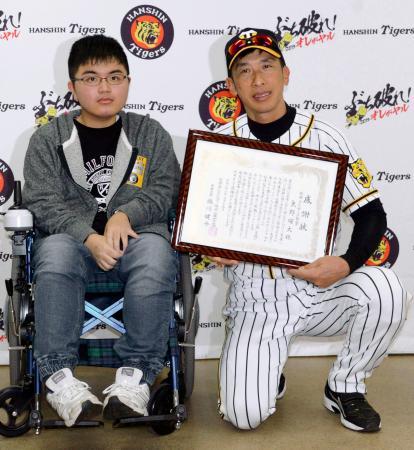 筋ジストロフィーの患者(左)から感謝状を受け取った阪神の矢野監督=15日、甲子園