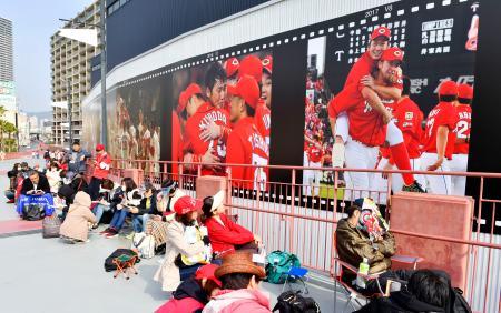プロ野球開幕戦が行われるマツダスタジアムの入場門付近で開場を待つファン=29日午前、広島市