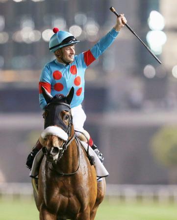 競馬のドバイ・ターフで優勝し、歓声に応えるアーモンドアイとクリストフ・ルメール騎手=30日、アラブ首長国連邦のメイダン競馬場(ロイター=共同)