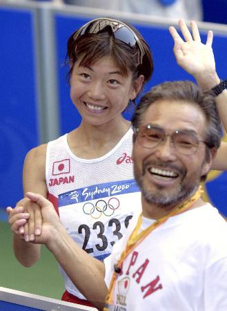 2000年9月、シドニー五輪女子マラソンで金メダルを獲得した高橋尚子選手と笑顔で握手する小出義雄コーチ(共同)