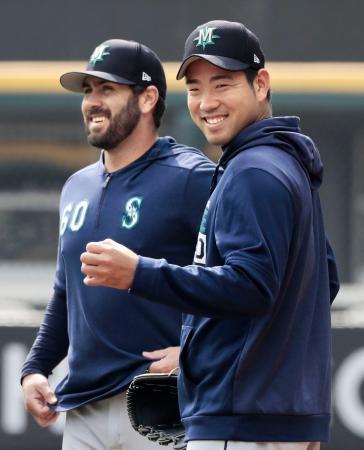 練習でチームメートと談笑するマリナーズ・菊池(右)=シカゴ(共同)