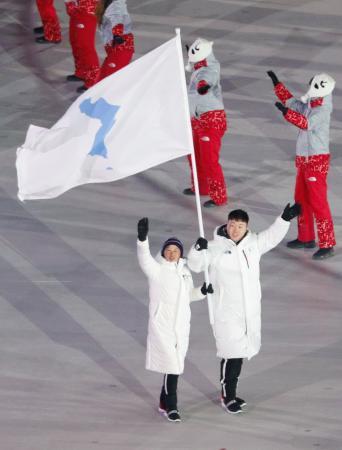 2018年2月、平昌冬季五輪の開会式で、「統一旗」を掲げ行進する韓国と北朝鮮の選手(共同)