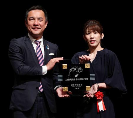 「三重県民栄誉特別功労賞」を授与され、盾を手に鈴木英敬知事(左)と写真に納まる吉田沙保里さん=13日午後、津市