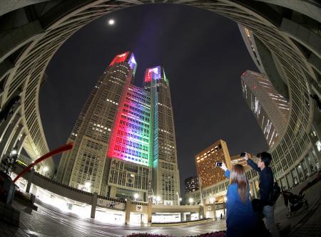 2020年の東京パラリンピック開幕まで500日となり、シンボルマーク「スリーアギトス」に使われている3色にライトアップされた東京都庁舎=13日夜(魚眼レンズ使用)