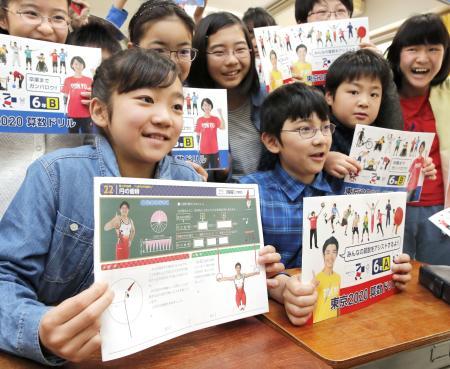 「東京2020算数ドリル」を手に笑顔の児童たち=17日午前、東京都世田谷区立笹原小