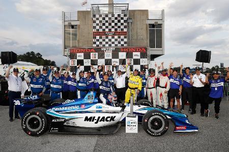 今季初勝利をポールトゥウインで飾り、自身のマシンに座りガッツポーズする佐藤琢磨(真ん中)。後ろはチーム関係者(C)Honda