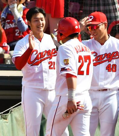 4回、田中広の2点打で生還した会沢(27)を迎える広島・床田(左)=マツダ