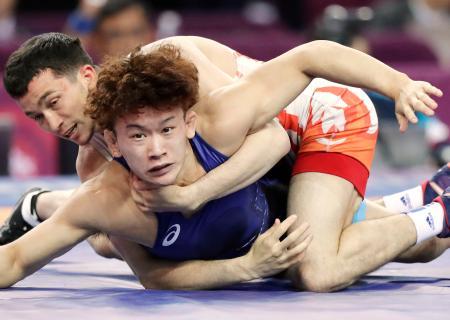 男子グレコローマン55キロ級決勝 ウズベキスタン選手(上)の攻めをこらえる片桐大夢=西安(共同)