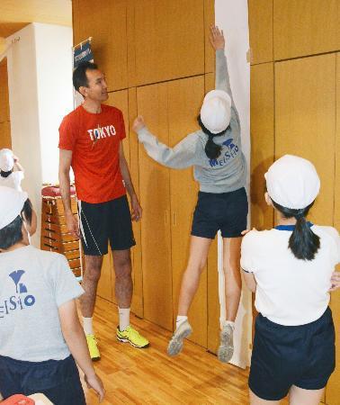 垂直跳びする児童とバレーボール元日本代表の大竹秀之さん(中央左)=13日、東京都中央区